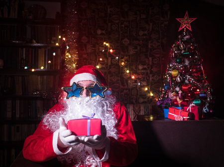 Santa Claus sitting in armchair at room decorated for Christmas. Winter holiday concept. Selective focus