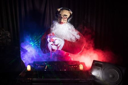 Funny 2019 year of pig concept. Dj Santa with pig mask at Christmas party mixing on New Year's Eve event. Disco lights in the background.