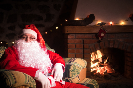 Santa Claus having a rest in a comfortable chair near the fireplace at home. Santa Claus in his house next to the fireplace Stock Photo