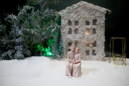 Toy artwork decoration. Happy New Year Celebration, Young Family standing in the Front Yard in snow with trees and small dollhouse. Selective focus Stock Photo