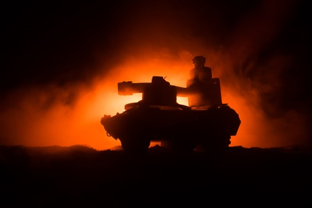 War Concept. Armored Tank Silhouette Below foggy fire sky at night. Attack scene. Toy decoration. Selective focus