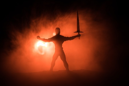 Medieval battle scene. Silhouette of warrior on dark toned foggy background. Night scene. Selective focus
