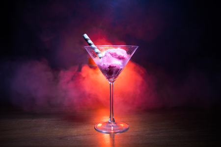 Martini glass filled with colorful fruit ice cream on dark background with toned light and fog. Selective focus Stock Photo
