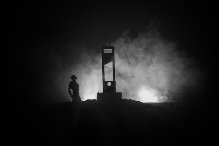Horror view of Guillotine. Human at guillotine on a dark foggy background. Execution concept Фото со стока