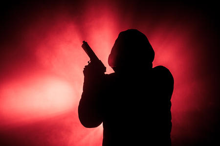 Silhouette of man with pistol ready to attack on dark toned foggy background or dangerous bandit holding gun in hand. Shooting terrorist with weapon theme decor Archivio Fotografico