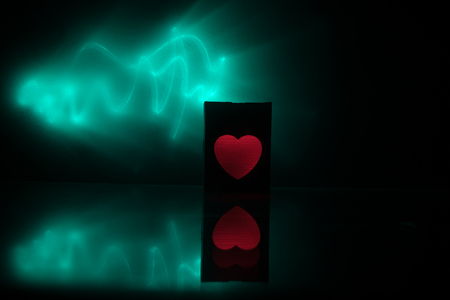 Dark table,Valentines day concept and love red shape heart with bokeh background, empty for text and placing products with copy space. Blurred glowing heart on a dark background with reflection
