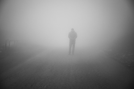 Man walking away on misty road. Man standing alone on rural foggy and misty asphalt road. Selective focus 版權商用圖片