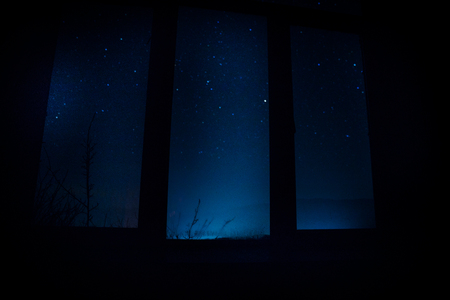 Night scene of stars seen through the window from dark room. Night sky inside dark room. Long exposure shot Stock Photo