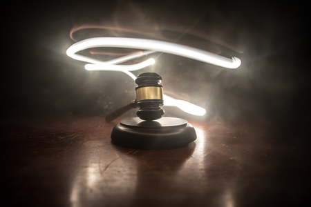 Law theme, mallet of the judge on wooden desk with Lady Justice Statue. Law gavel on dark foggy background with light. Selective focus Stock Photo