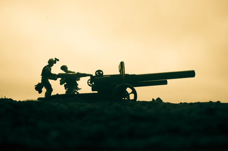 Battle scene. Silhouette of old field gun standing at field ready to fire. Creative artwork decoration. Selective focus Stock Photo