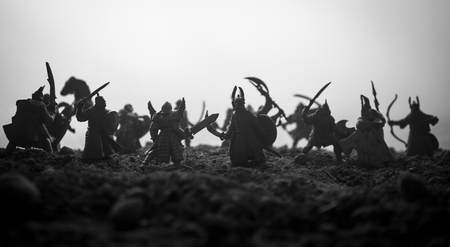 Medieval battle scene with cavalry and infantry. Silhouettes of figures as separate objects, fight between warriors on sunset foggy background. Artwork decoration. Selective focus Imagens