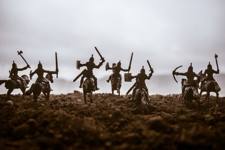 Medieval battle scene with cavalry and infantry. Silhouettes of figures as separate objects, fight between warriors on sunset foggy background. Artwork decoration. Selective focus Stock Photo