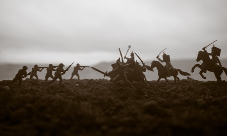 Battle scene. Military silhouettes fighting scene on war fog sky background. Creative concept. 20th century soldiers against medieval warriors. Artwork Decoration. Selective focus