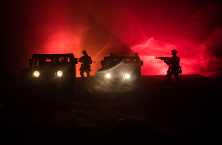 War Concept. Battle scene on war fog sky background, Fighting silhouettes Below Cloudy Skyline at night. Army vehicle with soldiers artwork decoration Stock Photo