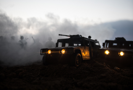 Militärpatrouillenwagen auf Sonnenunterganghintergrund. Kriegskonzept der Armee. Silhouette eines gepanzerten Fahrzeugs mit Soldaten, die zum Angriff bereit sind. Kunstwerk Dekoration. Selektiver Fokus