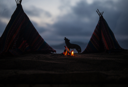 Artwork decoration creative concept. An old native american teepee in desert at the evening. Wigwam house indian style.