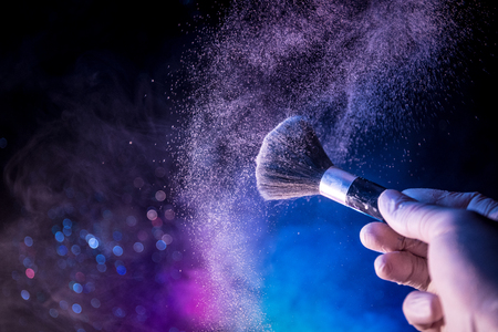 Makeup brush in hand with cosmetic powder on dark background with light and smoke. Powder splash on dark. Selective focus
