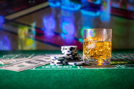 gambling, fortune, game and entertainment concept - close up of casino chips and whisky glass on table. Selective focus