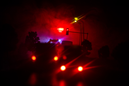 lighting of police car in the night during accident on the road. Artwork table decoration. Selective focus