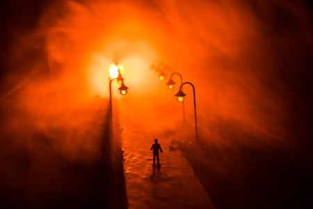 Artwork decoration. A man walking on road at night. The silhouette of a man standing in the middle of the road on a misty night. The glare of the street light against the fog sets a creepy mood.