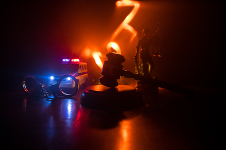 Law theme, mallet of the judge on wooden desk with Lady Justice Statue. Silhouette of handcuffs with police car on backside. Law gavel on dark foggy background with light.