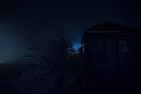 Vieille maison avec un fantôme dans la forêt la nuit ou maison d'horreur hantée abandonnée dans le brouillard. Ancien bâtiment mystique dans la forêt d'arbres morts. Arbres la nuit avec la lune. Lumières surréalistes. Concept d'Halloween d'horreur Banque d'images