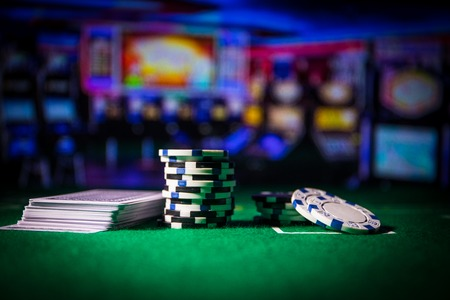 Cards and chips on green felt casino table. Abstract background with copy space. Gambling, poker, casino and cards games theme. Casino elements on green. Selective focus 스톡 콘텐츠
