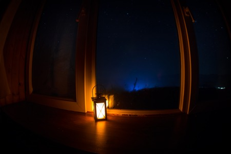Night scene of stars seen through the window from dark room. Night sky inside dark room viewing from window with old vintage lantern. Long exposure shot