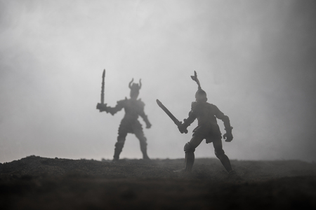 Medieval battle scene with cavalry and infantry. Silhouettes of figures as separate objects, fight between warriors on sunset foggy background. Selective focus Standard-Bild