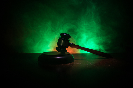 Law theme, mallet of the judge on wooden desk with Lady Justice Statue. Law gavel on dark foggy background with light. Selective focus Stockfoto