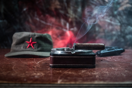 Close up of a Cuban cigar and ashtray on the wooden table. Communist dictator commander table in dark room. Army general`s work table concept. Artwork decoration Stock Photo