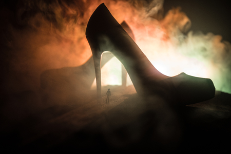 Artwork decoration. Silhouette of a man standing in the middle of the road on a misty night with giant high heel women shoes. Women power or women domination concept. Selective focus Stock Photo