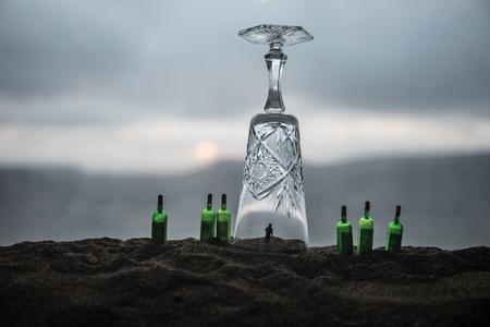 Concepto abstracto de alcoholismo. Gente bajo un cristal gigante como en prisión. Decoración de obras de arte creativas. Enfoque selectivo