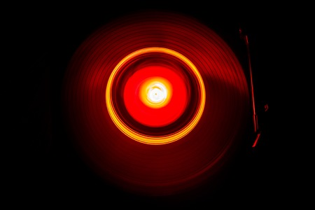 Music Dj concept. Trail of fire and smoke on vinyl record. Burning vinyl disk. Turntable vinyl record player on dark background. Selective focus
