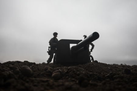 Battle scene. Silhouette of old field gun standing at field ready to fire. Creative artwork decoration. Selective focus 版權商用圖片