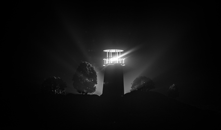 Artwork decoration. Lighthouse with light beam at night with fog. Old lighthouse standing on mountain. Table decoration. Toned background. Moonlighting. Selective focus Фото со стока