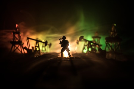 Artwork decoration. Oil war concept. Military silhouettes at oilfield with pumps and rigs. Misty colorful sky background. Armored vehicles fighting scene. Selective focus