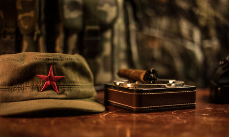 Close up of a Cuban cigar and ashtray on the wooden table. Communist dictator commander table in dark room. Army general`s work table concept. Artwork decoration Archivio Fotografico