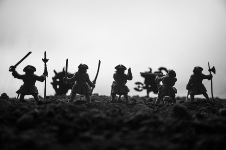 Battle scene. Military silhouettes fighting scene on war fog sky background. The musketeer soldiers Silhouettes below Cloudy Skyline at sunset. Artwork Decoration. Selective focus Stock Photo
