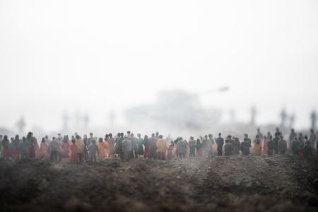 Gefangen vom feindlichen Konzept. Militärische Silhouetten und Menschenmenge auf Kriegsnebelhimmelhintergrund. Weltkriegssoldaten und gepanzerte Fahrzeuge bewegen sich, während die Leute verängstigt zusehen. Kunstwerk Dekoration. Selektiver Fokus Standard-Bild