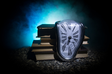 Time Concept. Distorted soft melting clock on the old books. With dark toned foggy background. Selective focus