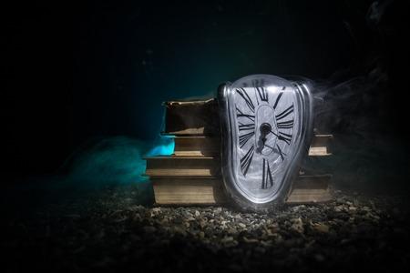 Concepto de tiempo. Reloj de fusión suave distorsionado en los libros antiguos. Con fondo brumoso en tonos oscuros. Enfoque selectivo