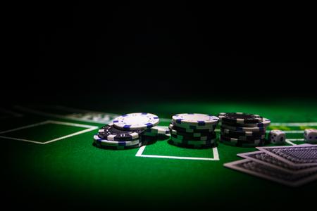 Carte e fiches sul tavolo del casinò in feltro verde. Sfondo astratto con copia spazio. Tema di giochi d'azzardo, poker, casinò e giochi di carte. Elementi del casinò su verde. Messa a fuoco selettiva Archivio Fotografico