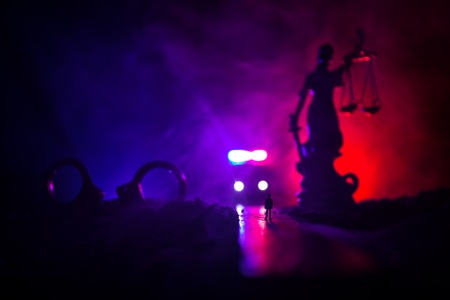 Legal law or crime concept. Man alone standing in the middle of the road on a foggy night. Artwork decoration with handcuffs, Statue of Justice and mallet of justice on toned foggy background. 版權商用圖片 - 119781436