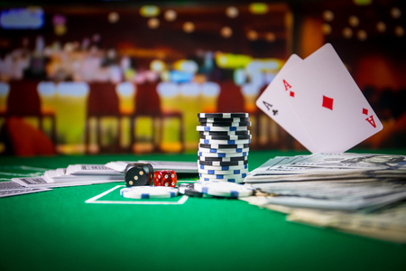 Cards and chips on green felt casino table. Abstract background with copy space. Gambling, poker, casino and cards games theme. Casino elements on green. Selective focus 版權商用圖片