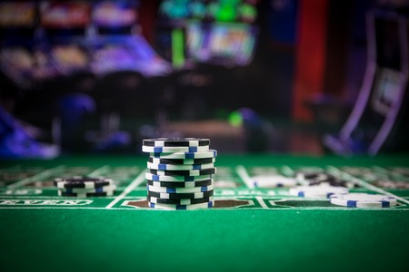 Cards and chips on green felt casino table. Abstract background with copy space. Gambling, poker, casino and cards games theme. Casino elements on green. Selective focus 免版税图像