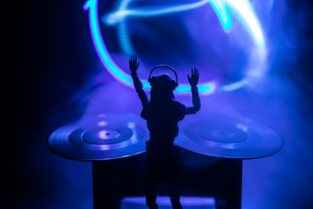 Dj club concept. Woman DJ mixing, and Scratching in a Night Club. Girl silhouette on dj's deck, strobe lights and fog on background. Creative artwork decoration with toy. Selective focus
