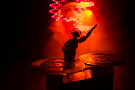 Dj club concept. DJ mixing, and Scratching in a Night Club. Man silhouette on vinyl turntable, strobe lights and fog on background. Creative artwork decoration with toy. Selective focus
