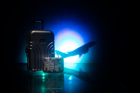 Summer vacation concept. Traveler suitcase with airplane in background. Artwork table decoration with empty space for your text. Focus on suitcase.