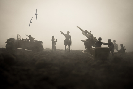 An anti-aircraft cannon and Military silhouettes fighting scene on war fog sky background. Allied air forces attacking on German positions. Artwork decorated scene. Selective focus 版權商用圖片
